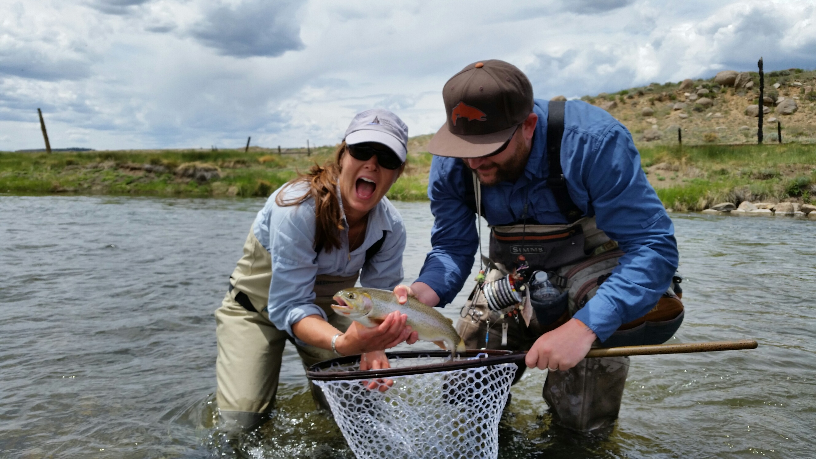 Ashley Tucker shown holding a cutbow trout while fishing the South Platte River in Colorado.