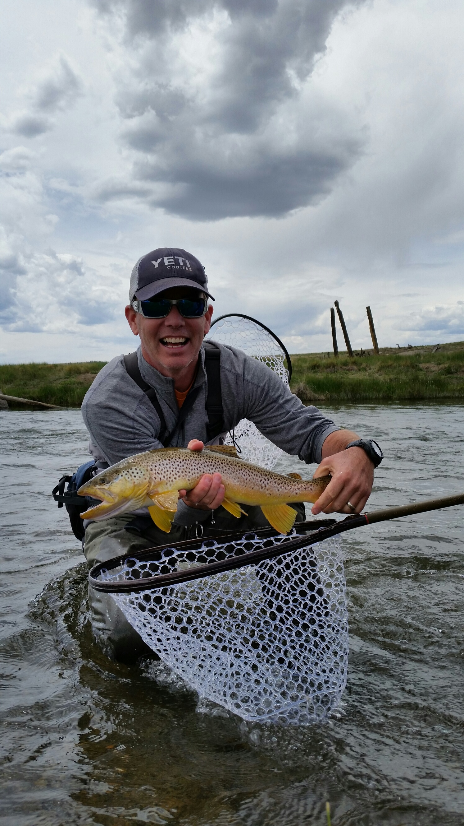 Keith Reis wearing a Mountainsmith Tour TLS on the Dream stream holding a brown trout