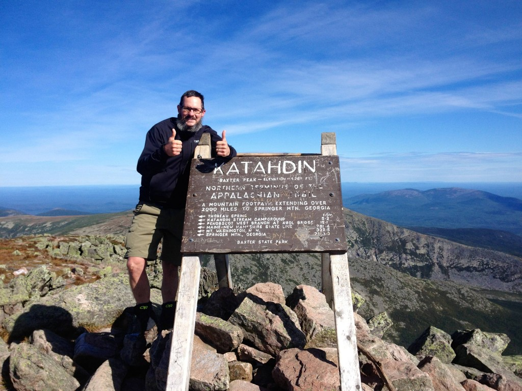 Appalachian Trail thru hiker slim jim aka chris spencer stands next to the sign at the peak of mount kathadin