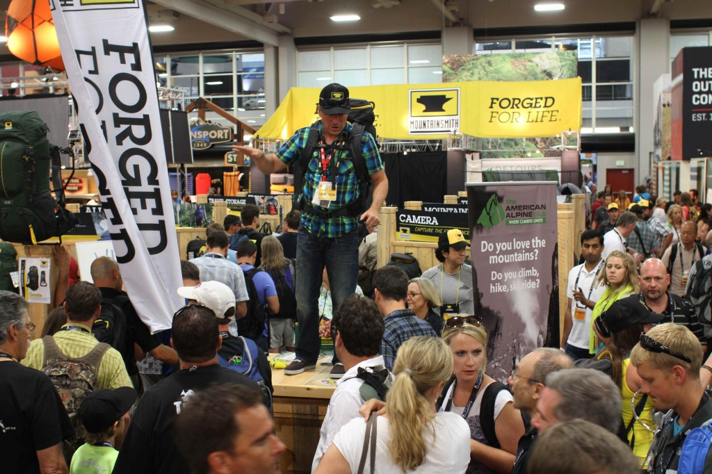 Andy Held of True Hero Events standing on the table at the mountainsmith booth at summer outdoor retailer