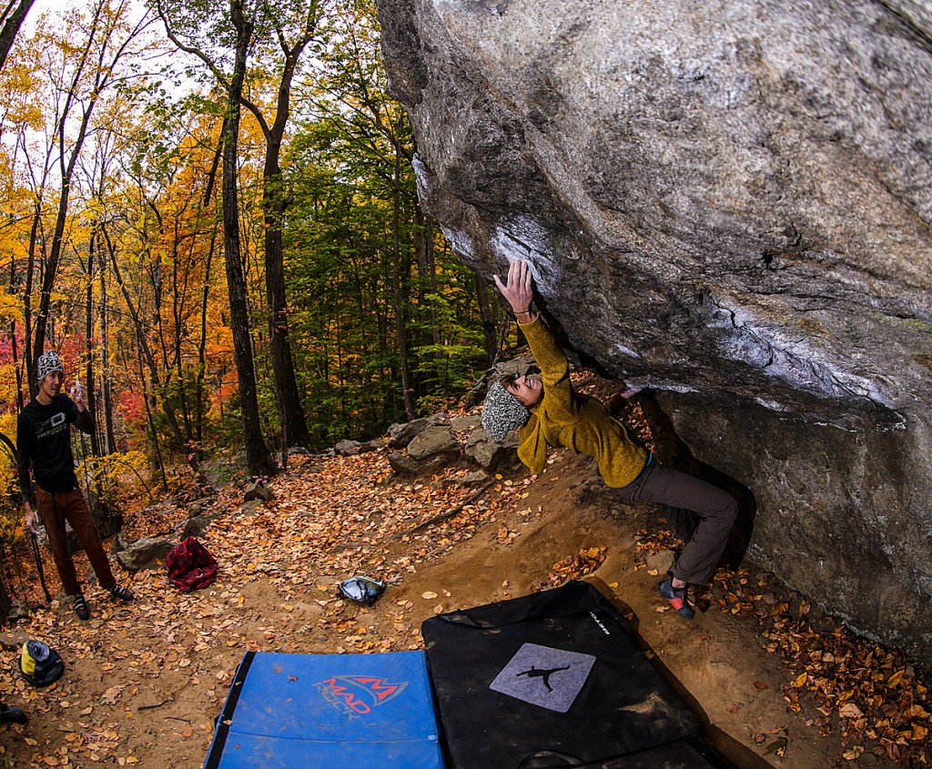 climber bouldering in Lincoln Woods, Rhode Island with a colorful autumn background