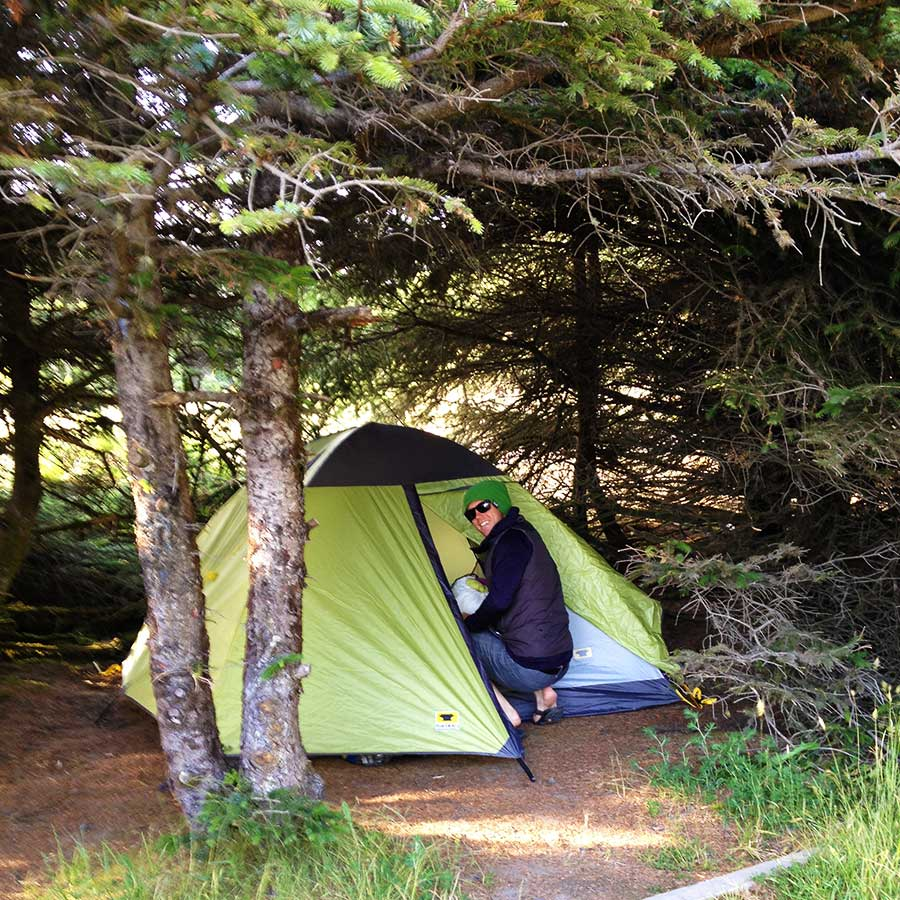 Alex Deibold sets up the Mountainsmith Genesee Tent under pine trees at Gold Bluffs Campground, California.