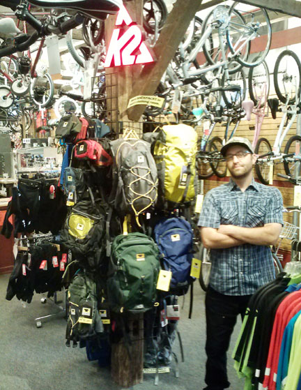 Greg from Onion River Sports standing proudly by the Mountainsmith pack display…