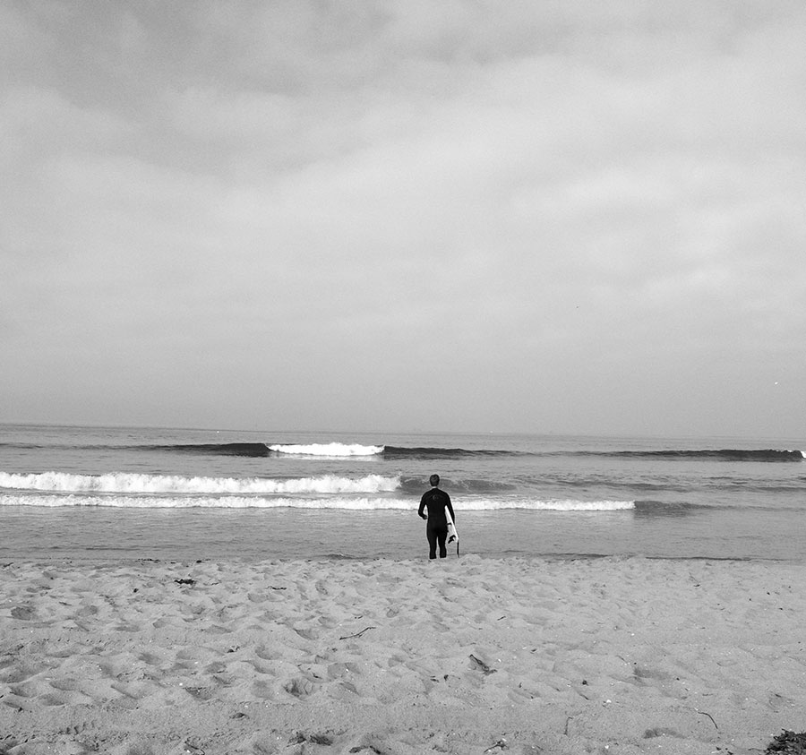 Alex Deibold going out for a surf at the 17th street break in Huntington Beach, California