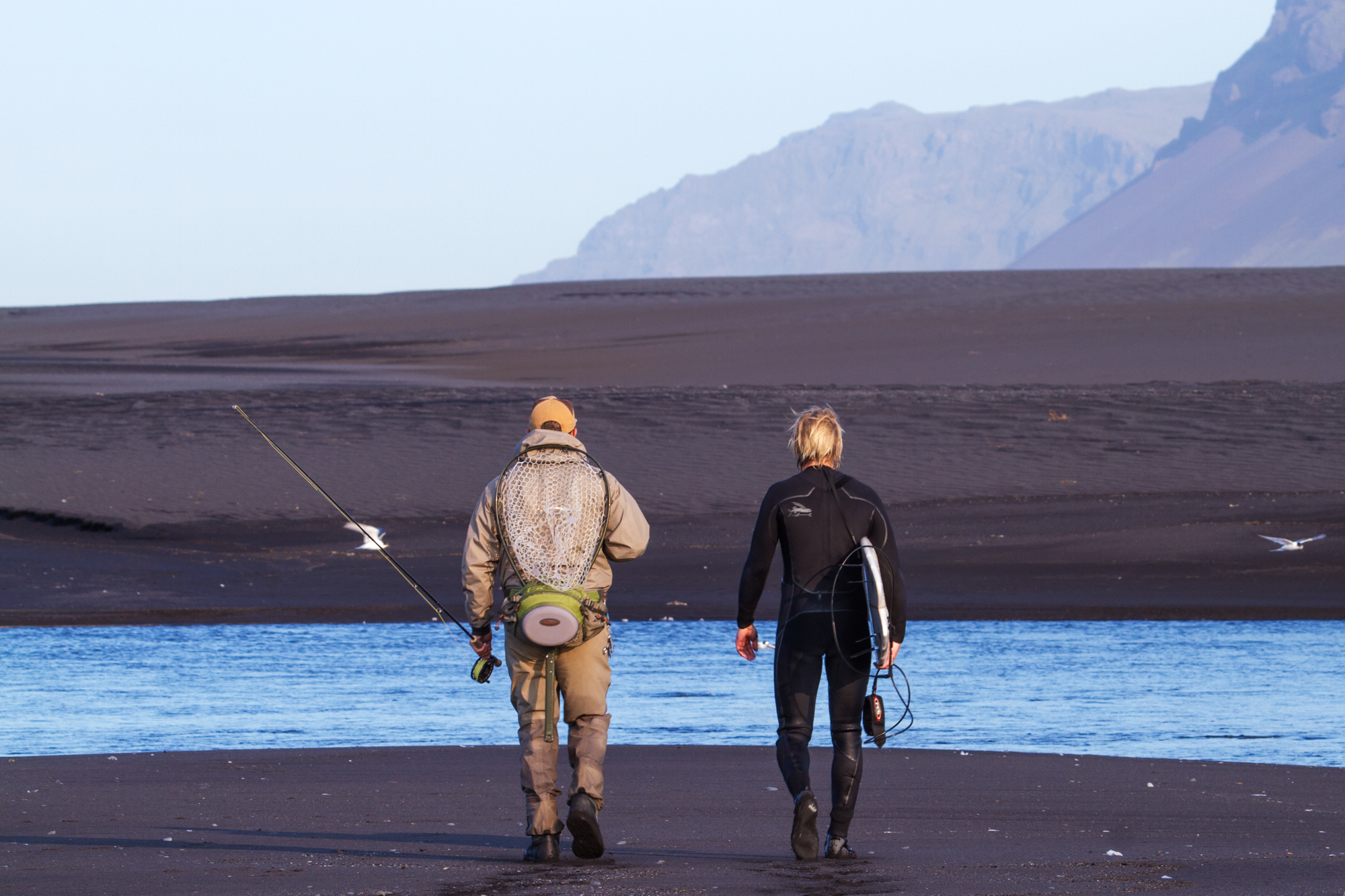 """a surfer and a fisherman walk along the beach in Iceland, from the movie """"YOW: Icelandic for Yes"""""""