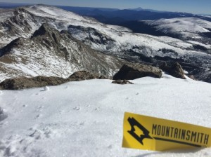 Mountainsmith logo in the snow with snowy mountain range in the background