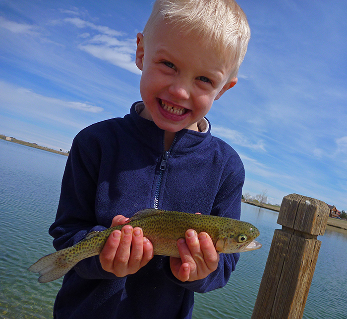 Kid with blue fleece jacket shown holding a trout on the river in Denver Colorado