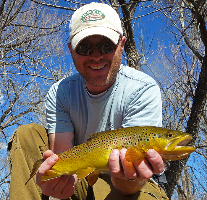 Jonathan Hill, writer, photographer and fly fisher and Mountainsmith Ambassador shown holding a trout while out fishing in Denver, Colorado