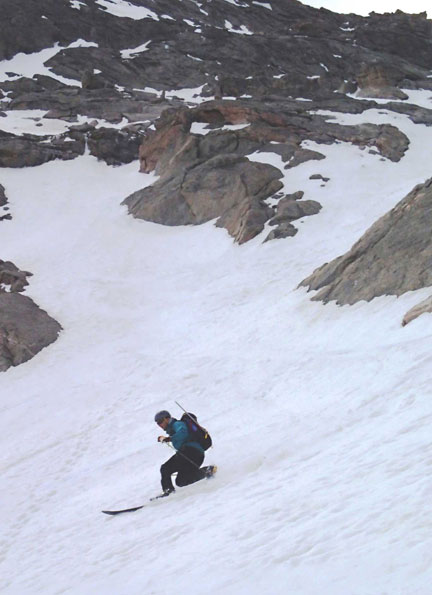 Jay Getzel laying down some fun telemark turns as the couloir opens into the snowfield below on Mt. Evans