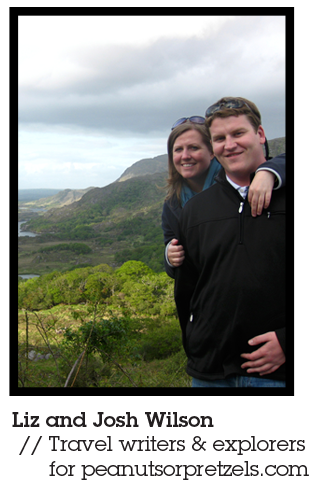 Liz and Josh Wilson Mountiansmith Brand Ambassadors and travel writers for peanutsorpretzels.com, pose together in front of a lush green landscape