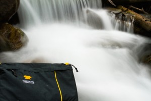 Mountainsmith Tour FX camera lumbar pack in front of a waterfall