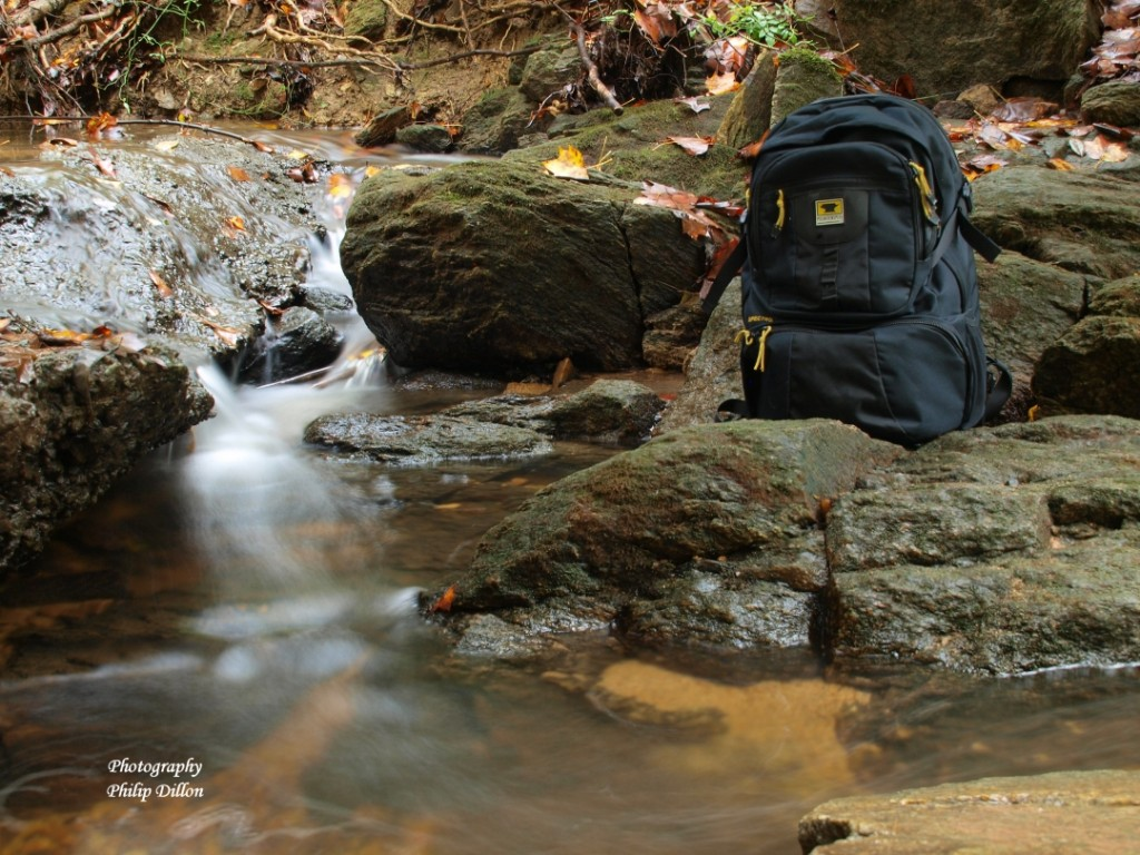 The Mountainsmith Spectrum Photography backpack next to a waterfall shot by Phil Dillon with a long exposure