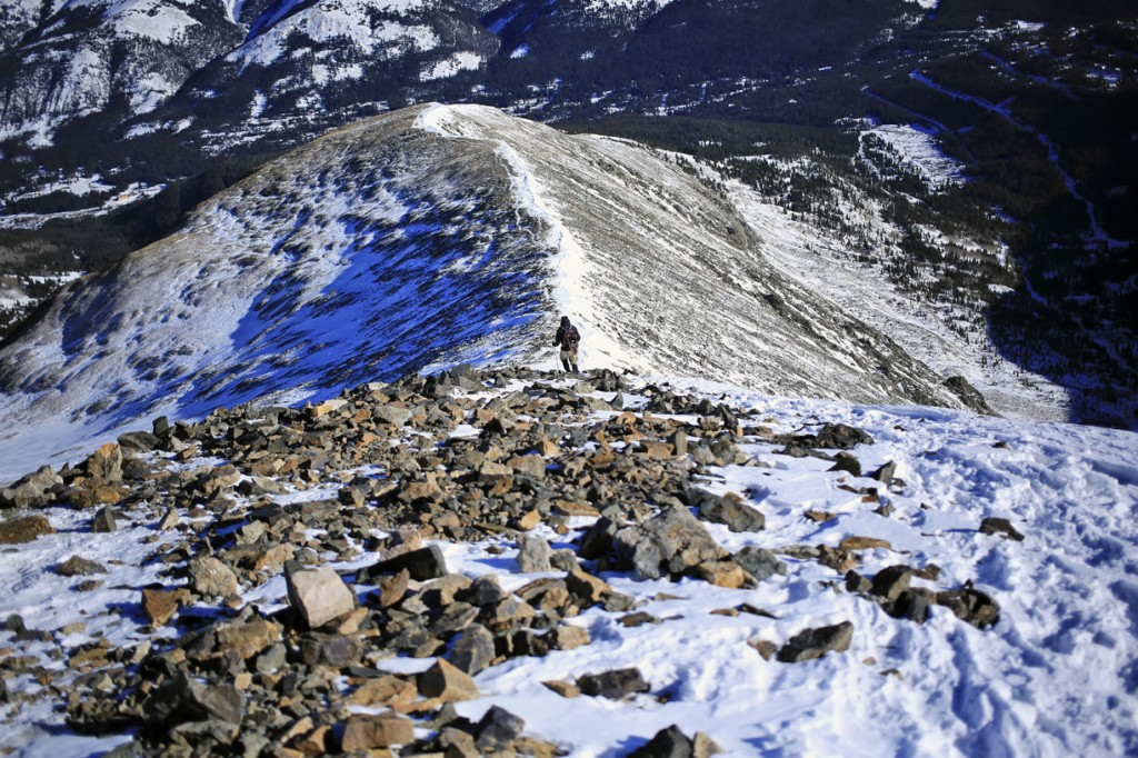 a hiker approaches the summit along the ridge line of Quandary Peak during winter in Colorado