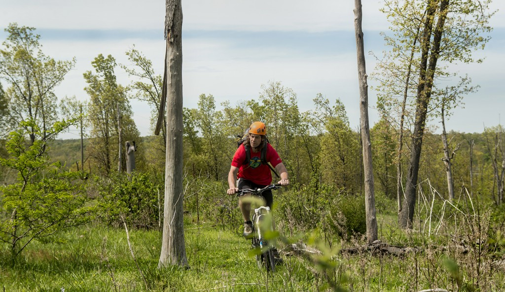 Curtis Savard riding a mountian bike through a cow pasture in Missouri, image by Aaron Codling