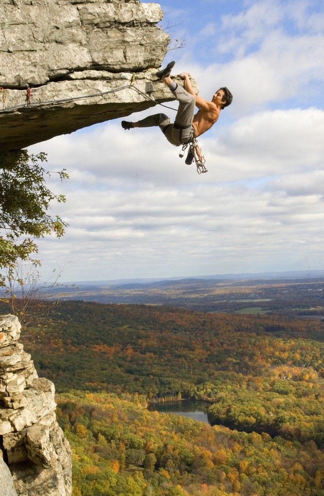 a climber swings his leg up over a rock on an overhang