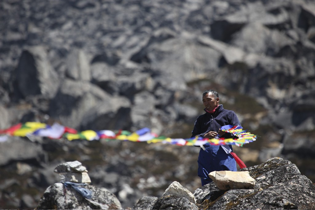 A man holds prayer flags at a Puja ceremony at a Himalayan Basecamp.