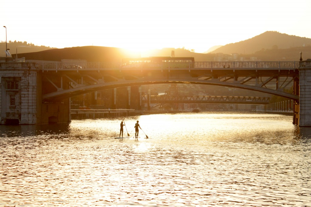 """Two SUPers paddling down """"La Ria"""" at sunset in Bilbao"""