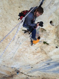 Andy Mann shooting photography while hanging off a rock wall with his Mountainsmith lumbar pack