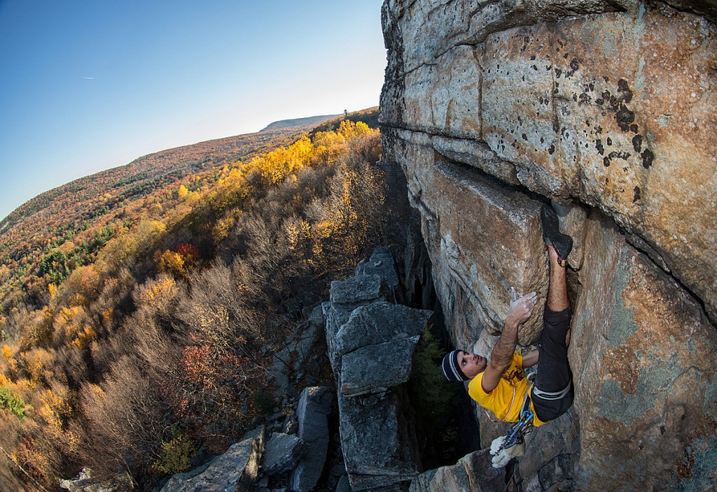Rock climber toe hooking a hidden wall in New York with colorful autumn background. Catching the golden hour light